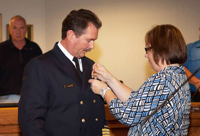 Martie Napier pins the Valley Center Fire Department's chief's pin on her husband, Josef Napier, now officially VC Fire Chief at Thursday night's meeting of the fire board.—Photo courtesy of Lenny Kerbs Custom Photography