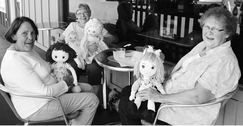 """You might think this to be a meeting of the local Raggedy Ann Club, but the ladies in the foreground, Susan Upson and Dorothy Conley from Oregan are just admiring of the handiwork of Lenore Cobbs (in the back, holding two dolls). These are the first ones she has produced. """"I'll make more if they pay enough!"""" she said. If you want to talk to her about it, call 760-331-3268."""