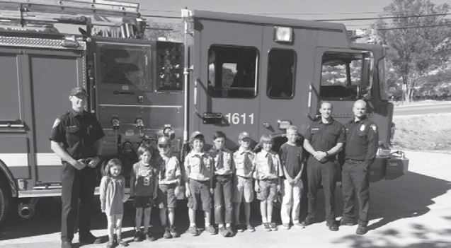 The local Scout troop poses with firefighters of Valley Center Fire Protection Distrct at the Lilac Station. The firefighters set up a bouncy house for the kids.