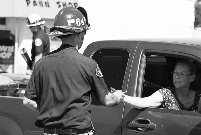 A firefighter from Rincon Station # 64 collects money for Relay for Life at the corner of Cole Grade & Valley Center Rd. The volunteers raised $2,500 in two and a half hours. Photo courtesy of Kerbs Custom Photography.