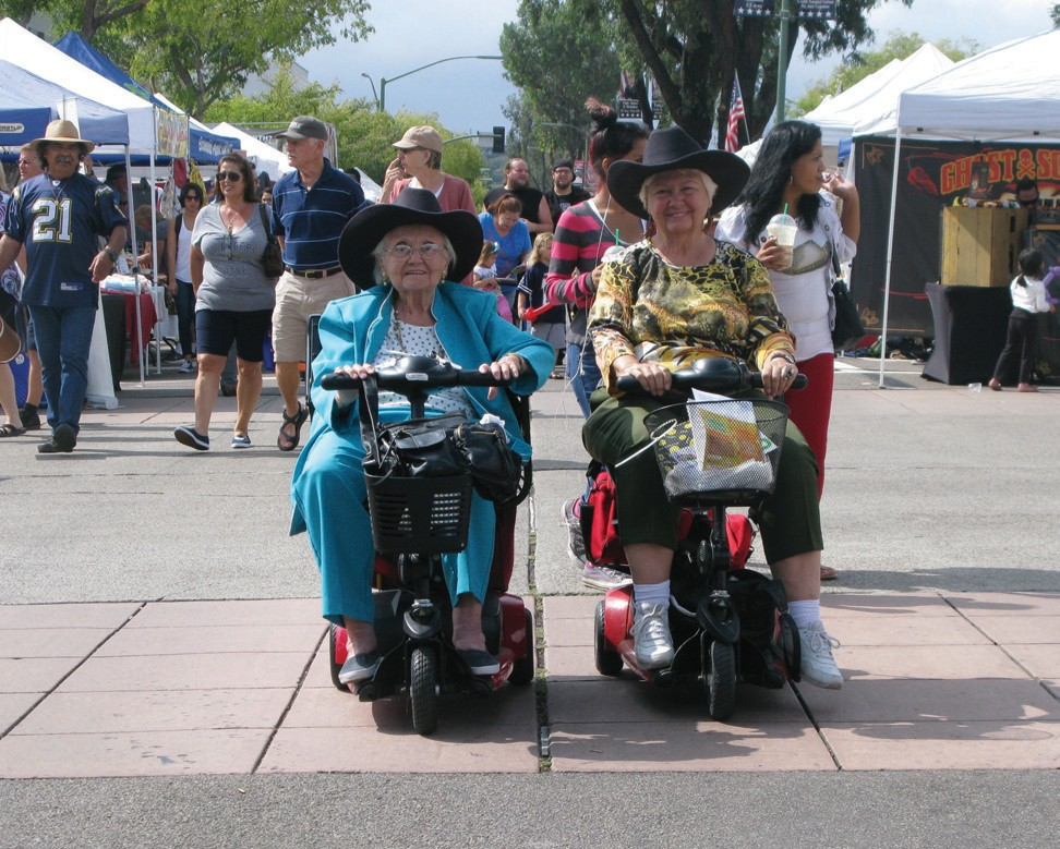 Jean Baxter and Barbara Saad of Escondido tool down Grand Avenue at the Street Faire on Sunday. Barbara said her personal scooter usually sports a horse's head and a horsetail on the back. The event was a great success, with more than 500 booths selling everything from barbecue sauce to jewelry. For more photos, turn to Page 2.
