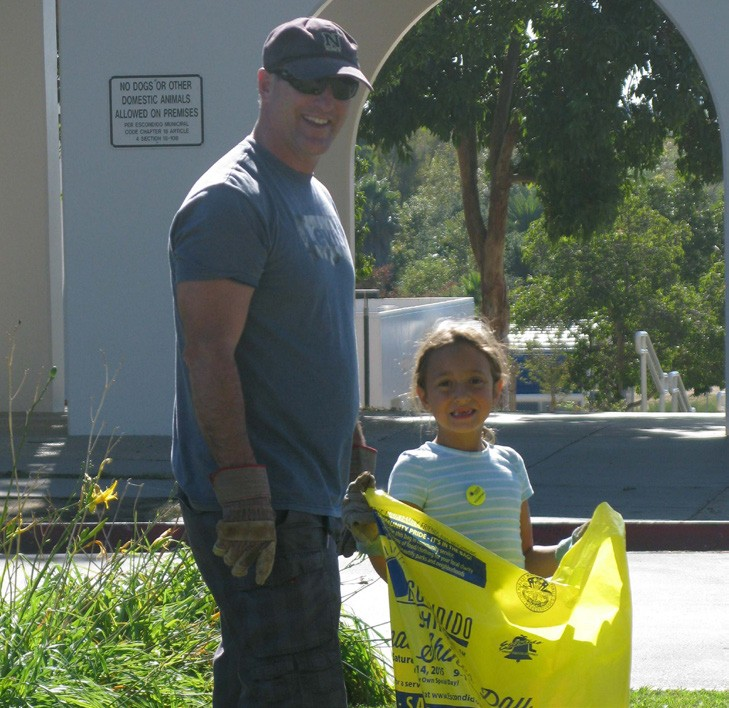 Mark Cappelletti and his daughter Gianna pick up litter on Amphitheatre Drive at Kit Carson Park. The event drew 600 participants to 10 Escondido parks.