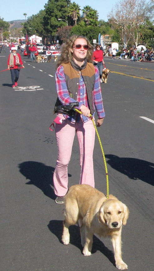 A member of the San Diego Golden Retriever Meetup Group is drawn forward by her dog in the bright, sunny weather of the 65th Annual Christmas Parade, which, orgainzers said, is the longest running community event in North San Diego County.