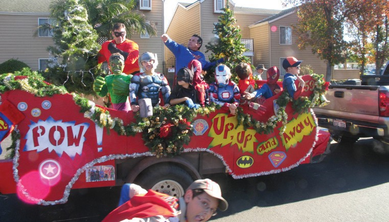 "Dads and members of Cub Scout Troop 659 actually conformed to the theme of the event, ""A Superhero Christmas,"" sporting costumes and striking heroic poses on their homemade float."