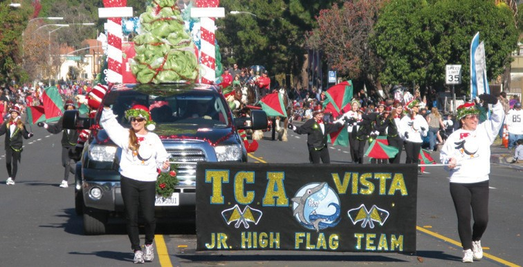 The TCA Vista Junior High School Flag Team waved and weaved along on the pa­rade route near Lincoln Elementary School on Broadway at last Saturday's Christmas parade.