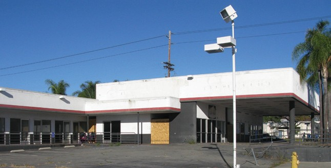 The former service building, above, for Toyota of Escondido has sat empty for several years. Neighbors say homeless people have been living in and around the site's empty repair bays and buildings.