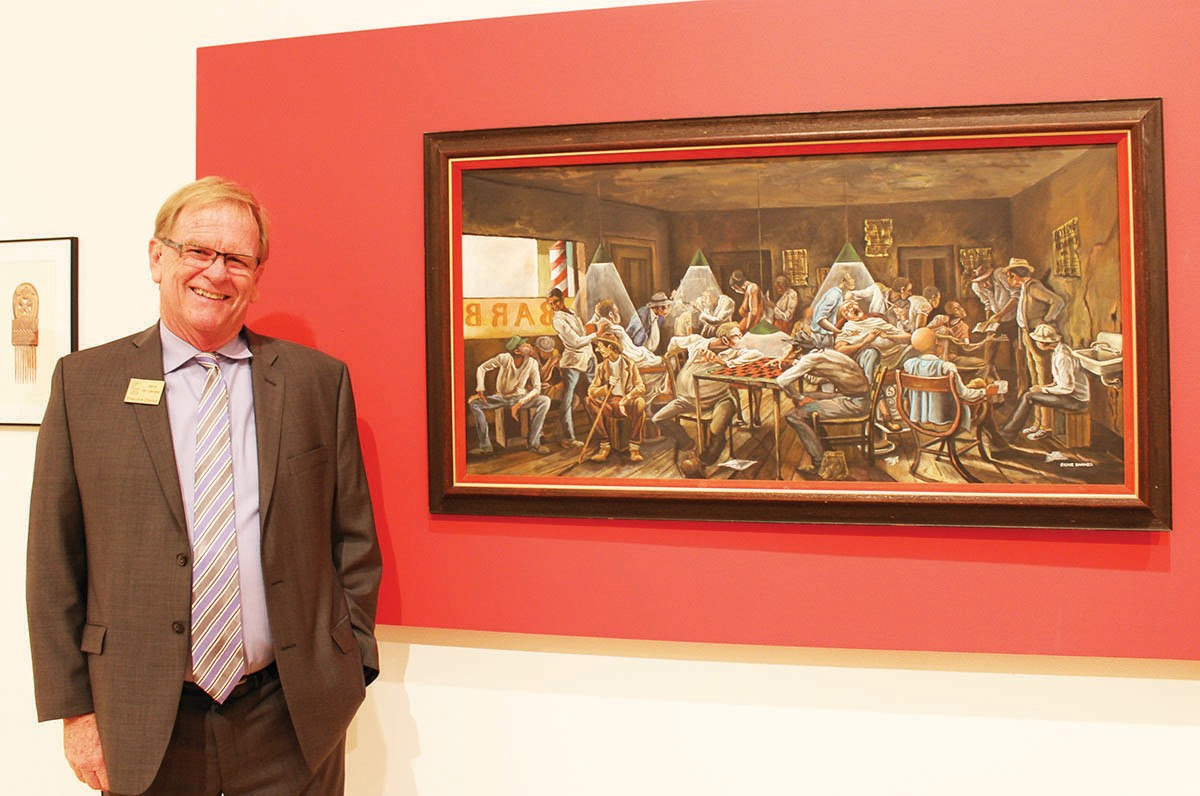 RIGHT: Jerry Van Leeuwen, executive director of the Center, next to one of his favorite pieces in the exhibit. Friday he marveled that the exhibit had brought out one of the largest groups of attendees for an opening night reception that he could remember.