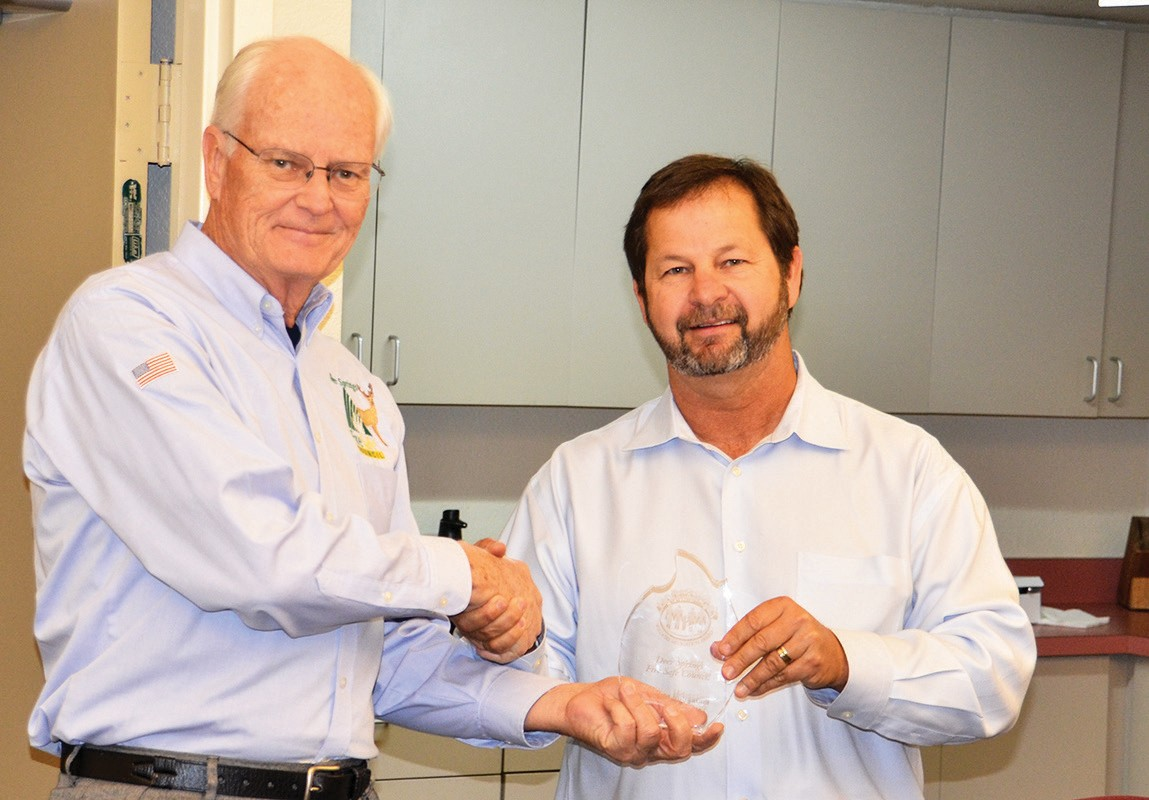 Deer Springs Fire Safe Council President Craig Cook, left, receives the national Wildfire Mitigation Innovation Award from Deer Springs Fire Marshal Sid Morel, who was acting on behalf of the national Wildfire Mitigation Awards
