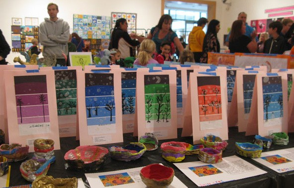 Festival-goers take in an exhibition of ceramics and visual art.