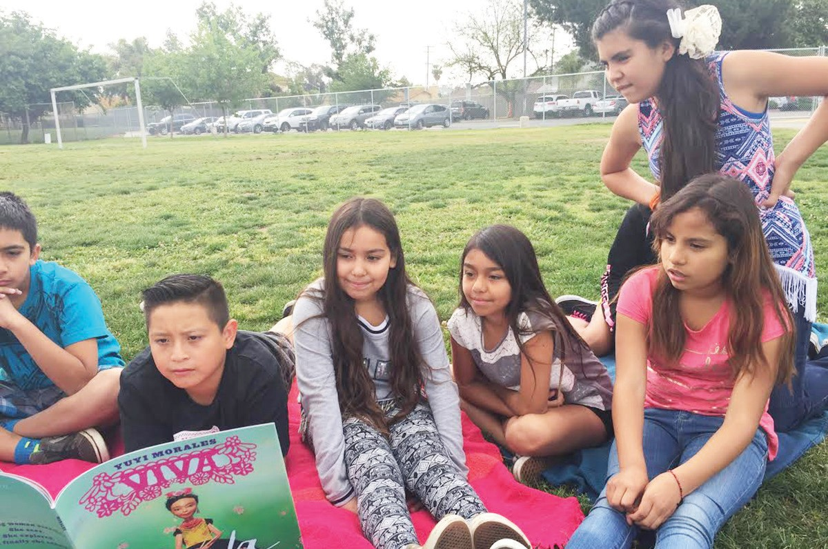 """Students participating in Family Friday, where family members read the book """"Vida Frida"""" in either English or Spanish."""