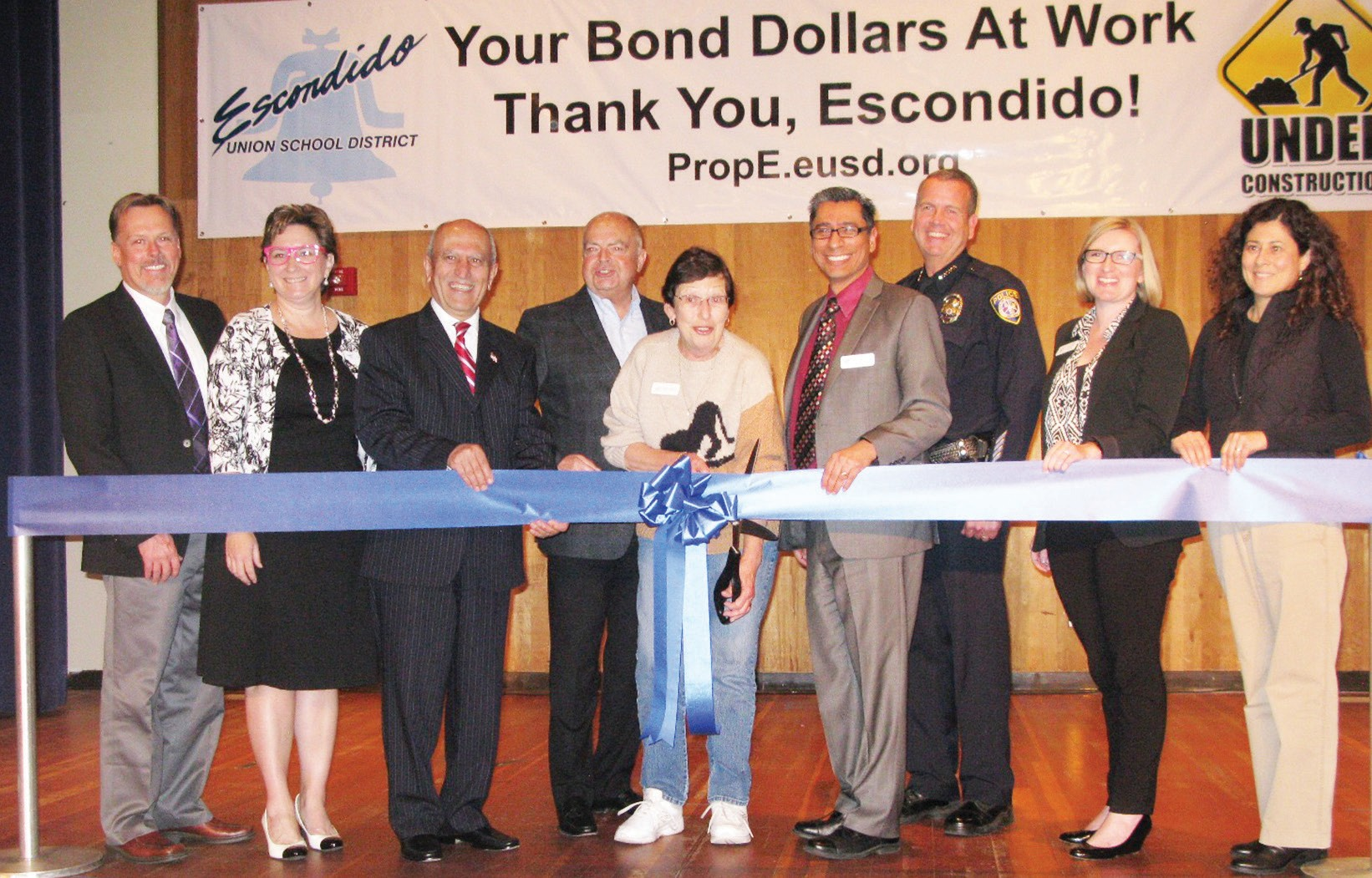 School Board Chairman Joan Gardner cuts the ribbon in celebration of the fencing projects at four Escondido Union School District schools. From left are Dr. Gary Al­tenburg, EUSD Board Clerk; Paullette Donnellon, EUSD Board Member; Mayor Sam Abed; Kirk Effinger, Citizen's Oversight Committee Chairperson; Joan Gardner; Dr. Luis Ibarra, EUSD Superintendent; Craig Carter, Chief of Police, Zesty Harper, Board Vice-President; Olga Diaz, Escondido Councilwoman. LEFT: Michael Taylor, assistant superintendent and emcee of the event. Photo by Doug Green