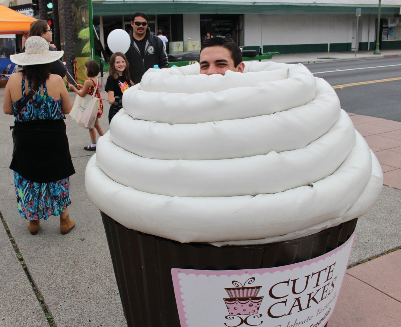 A human cupcake out advertising for Cute Cakes.