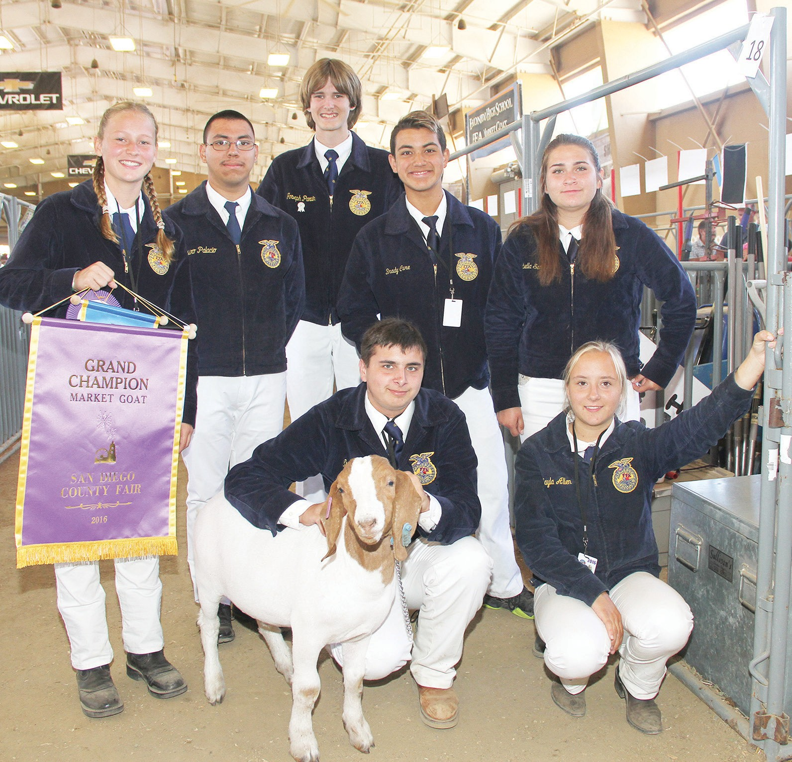 Students from Escondido, (kneeling from left) Evan Hildreth, age 16, with his goat Lucky and 15-year-old Cassandra Coffey; (standing, from left) Award winner Samantha Christensen, age 14, Mauro Palacio, age 17, Joseph Parvin, age 17, Brady Cure, age 14 and Isabella Sanchez, age 15, gather in the barn prior to the goat auction. Photo by Carla Van Wagoner