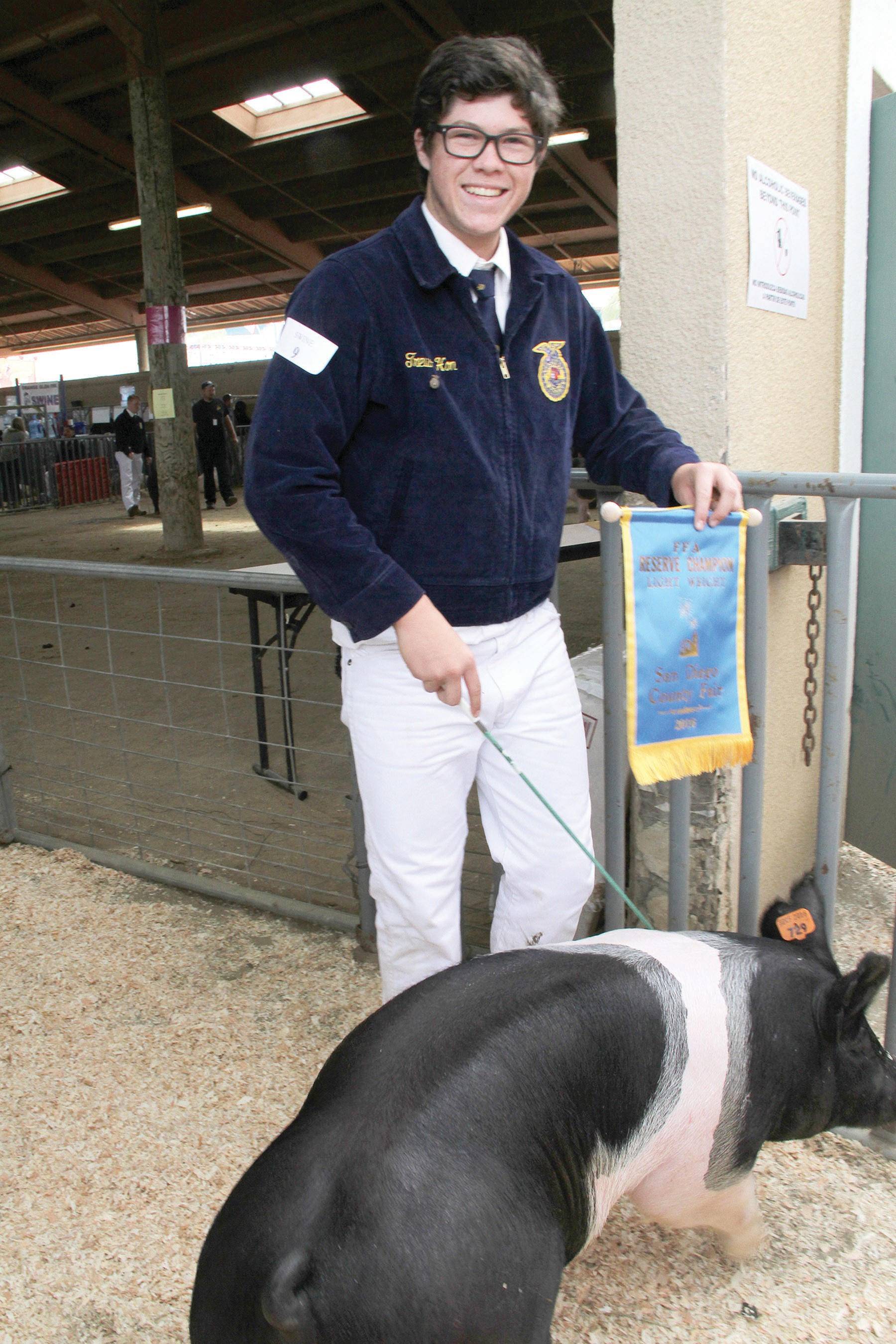 Escondido resident Trevor Hon with his 235 lb. pig exit the auction block. Photo by Carla Van Wagoner