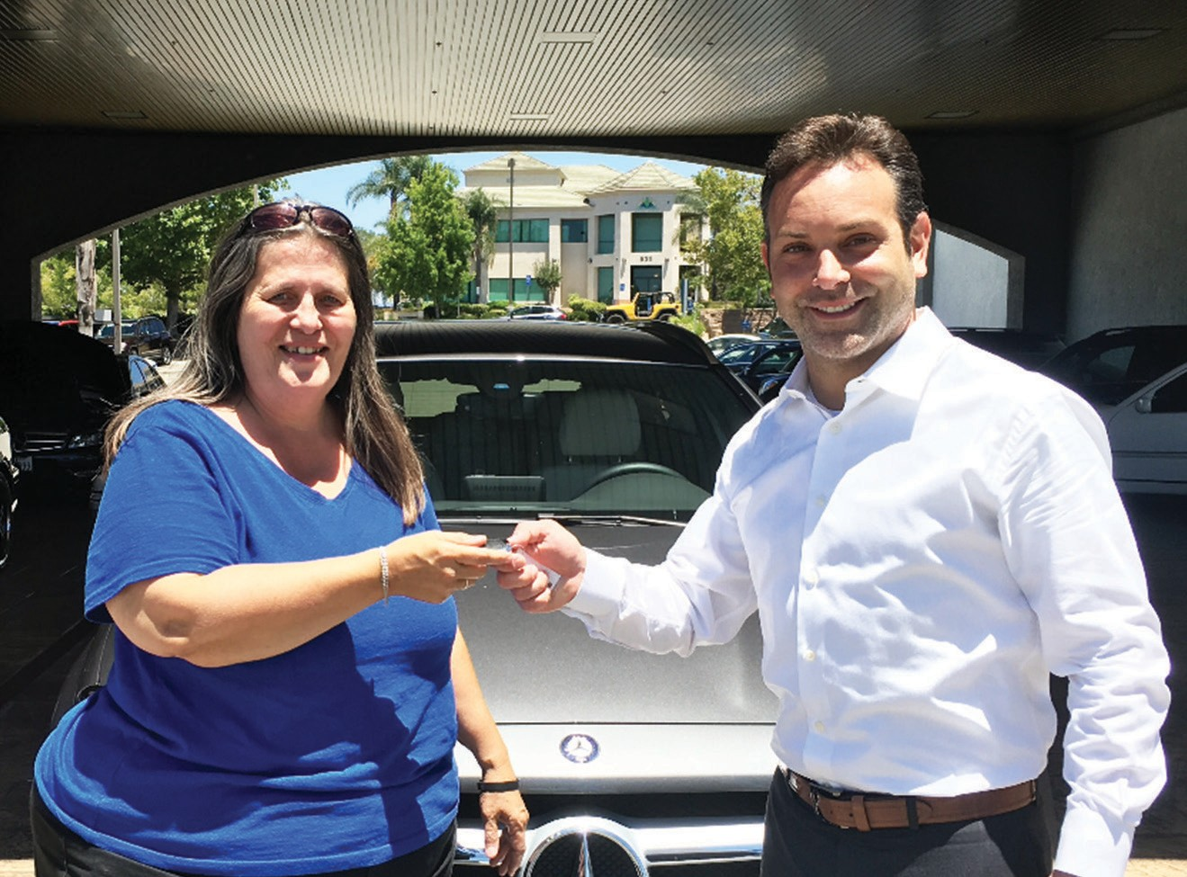 Volunteer Judy Corasaniti gets the key to a Mercedes-Benz from Mercedes Benz of Escondido General Manager Jason Cestaro.