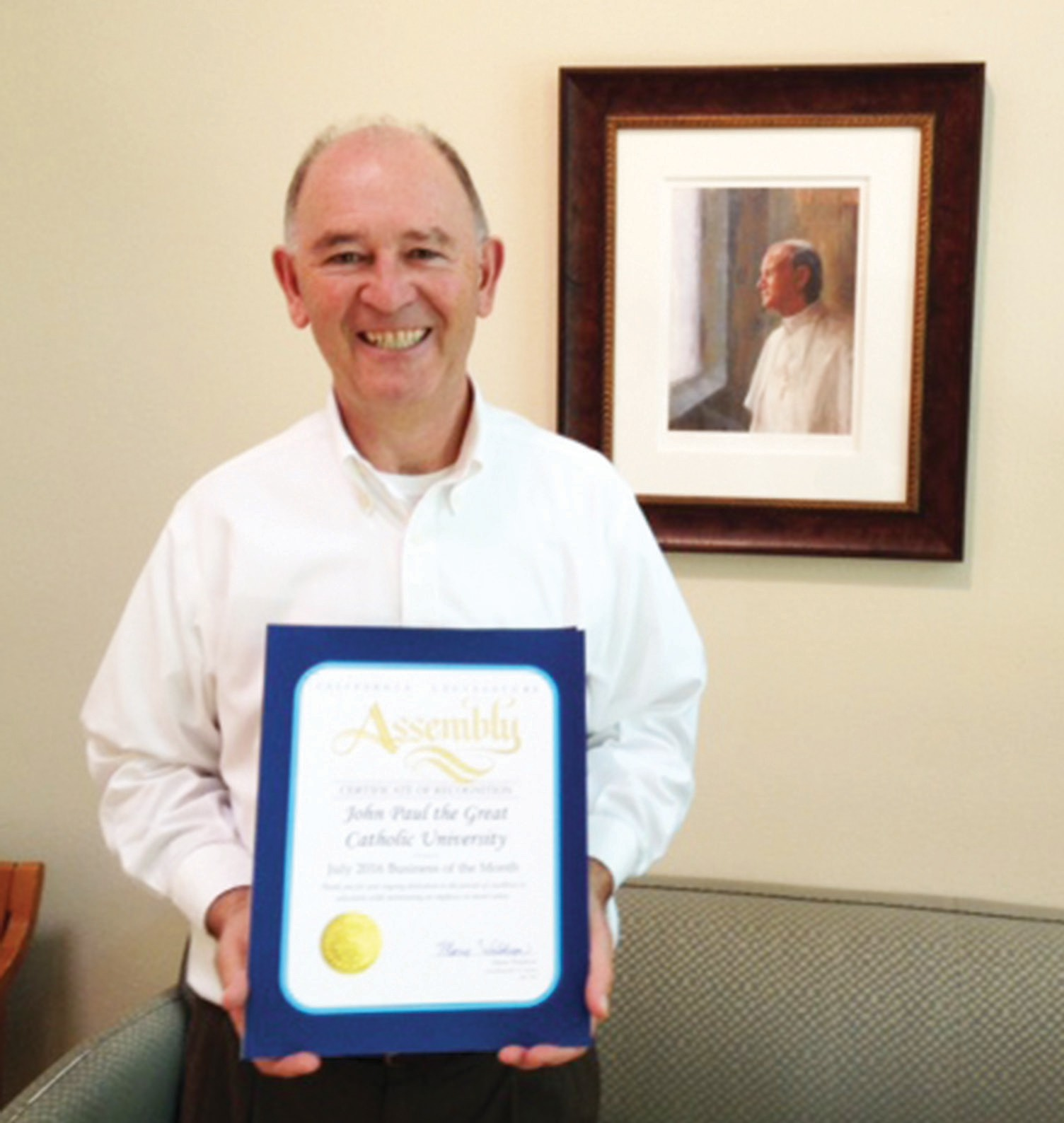 President Dr. Derry Connolly accepts a certificate from Assemblywoman Marie Waldron designating John Paul the Great Catholic University Business of the Month for July, 2016.