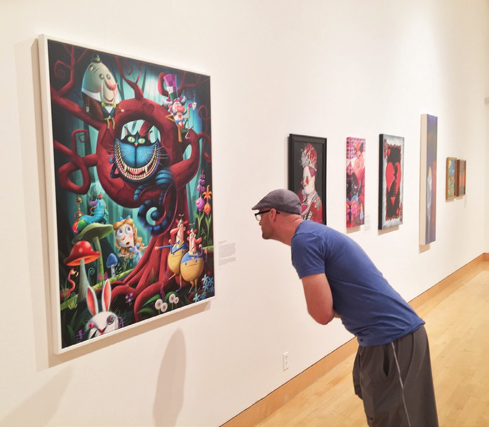 A museum visitor enjoys the details of the Cheshire Cat and other characters in this painting.