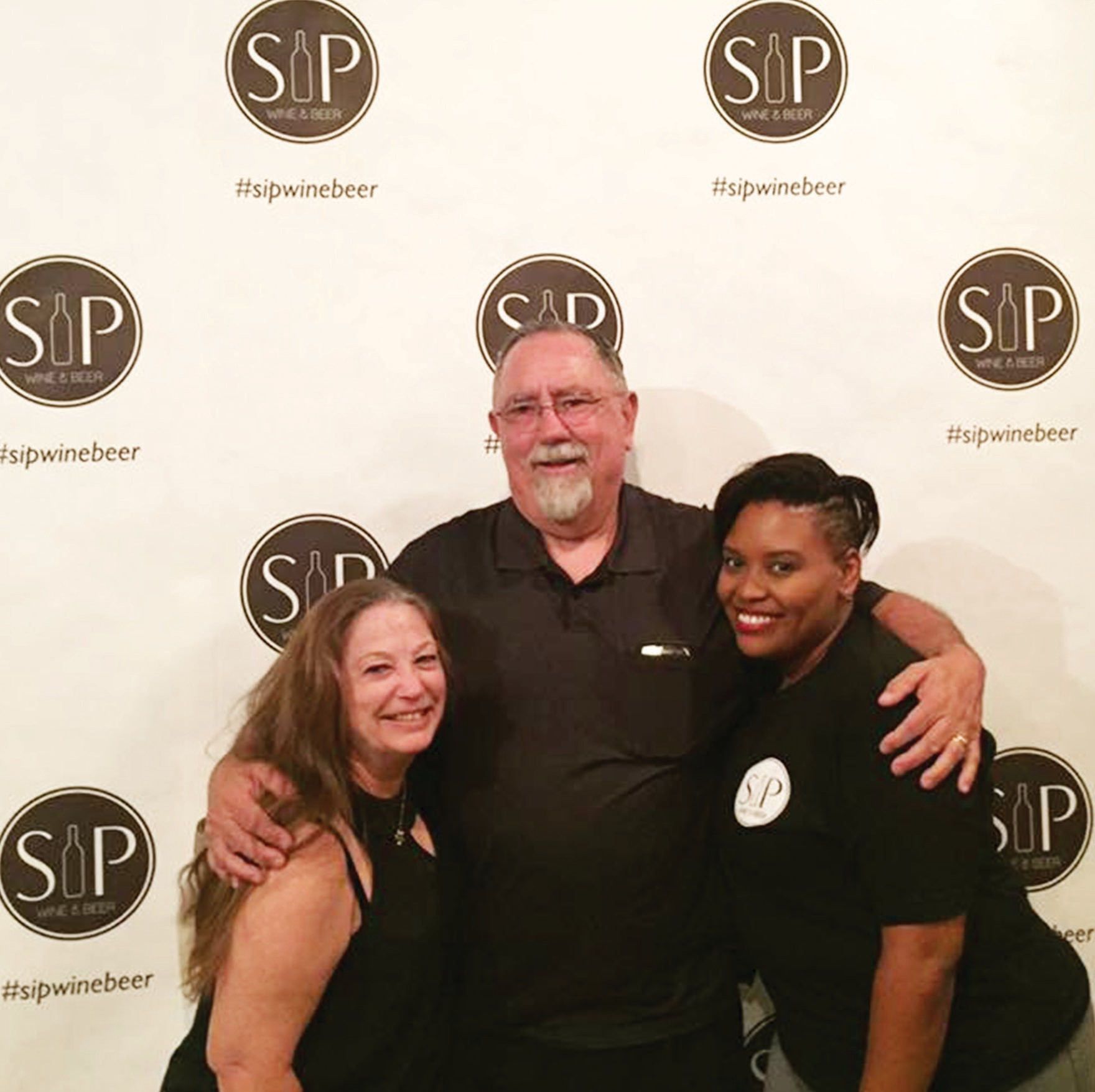 "In front of the ""Selfie"" spot at Sip, Wine & Bear. From left, Susan Baldwin Wilkin­son, Skip Wilkinson, and Cassandra Schaeg."