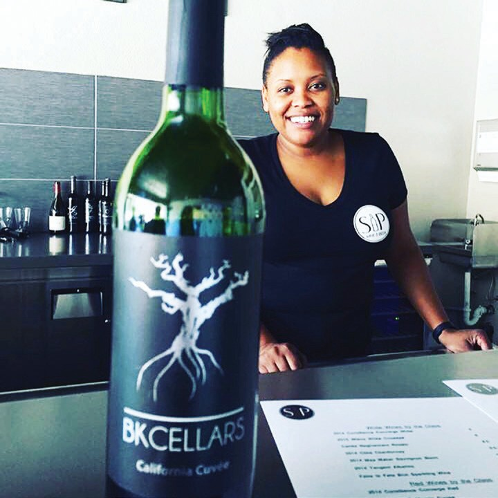 Cassandra Schaeg, co-owner of the Sip, Wine and Beer, with one of the signa­ture wines that they feature from a local winery, BK Cellars.