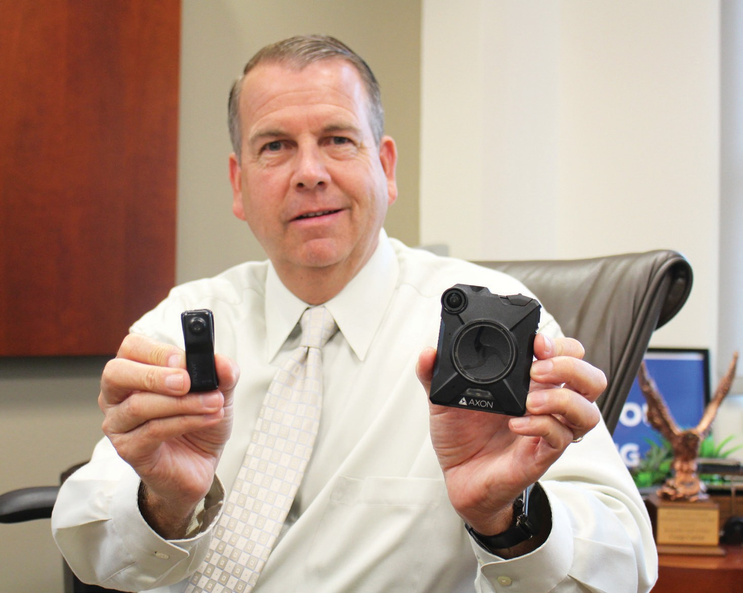 Chief Craig Carter shows the difference between the small and relatively primitive body cameras that officers wore as recently as four years ago and the newer, more sophisticated versions which have larger storage, higher resolution and better sound.