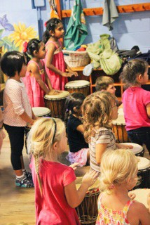 Right: Children learn how to play the bongo drum at a recent Root Series activity.