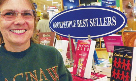 Brookes stands in front of her book, Linked Lives, displayed on the Best Sellers table at the largest independent book store in Texas - BookPeople in Austin.