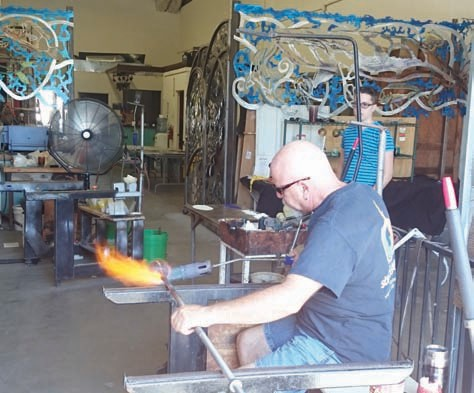 James Stone blowing glass to create candleholders for a custom order.