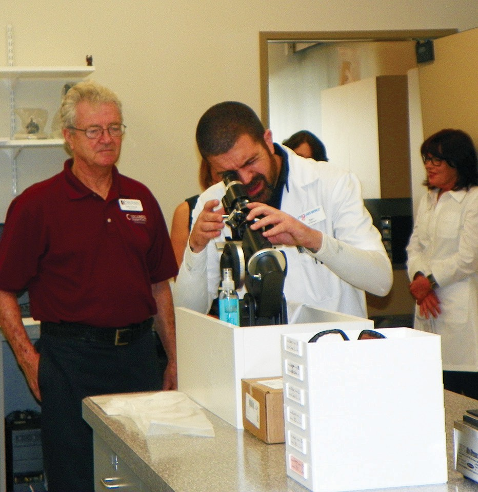 The lab manager shows how he uses one piece of equipment in the Eyeglass World lab.