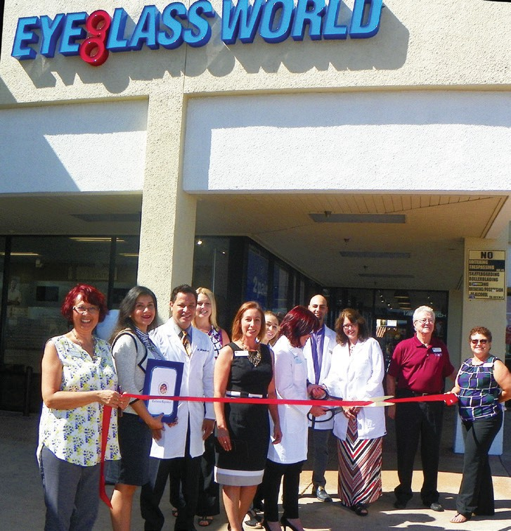 Carrie Villvalva, General Manager of Eyeglass World, prepares to cut the ribbon surrounding by a supportive crowd.
