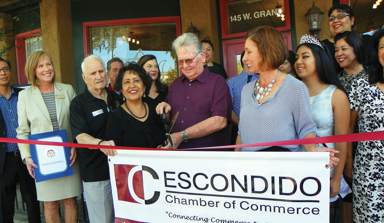 The official ribbon cutting, with Louisa Magoon (front) and many other VIPs from the Chamber joining in. They include (from left) Dr. Luis Ibarra, Marie Joyce from Assemblywoman Marie Waldron's office, Don Burgett from Congressman Duncan Hunter's office, owner Louisa Magoon and Bob Magoon, Rorie Johnston, chief executive office of the Chamber, Miss Escondido Valeria Hernandez (behind Johnston), Rosa Ruiz, Joe Coyle, Chamber Board Chairman Linda Bailey.