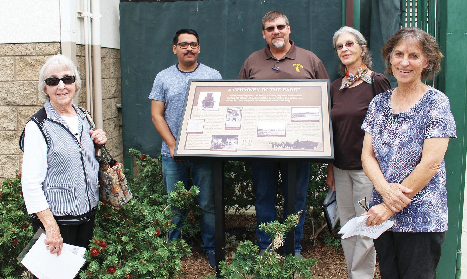 "Posing with the new ""A Chimney in the Park"" interpretative sign are (from left) Ruth Collings, Carlos Tirado, Dan Young, park superintendent, Julie Johnson Lavelli, a Porter granddaughter (the Porters being the family that donated the land for Kit Carson Park to the city) and Alexa Clausen, who spear-headed the effort to install the interpretative sign near the flagpole of the park's main building complex."