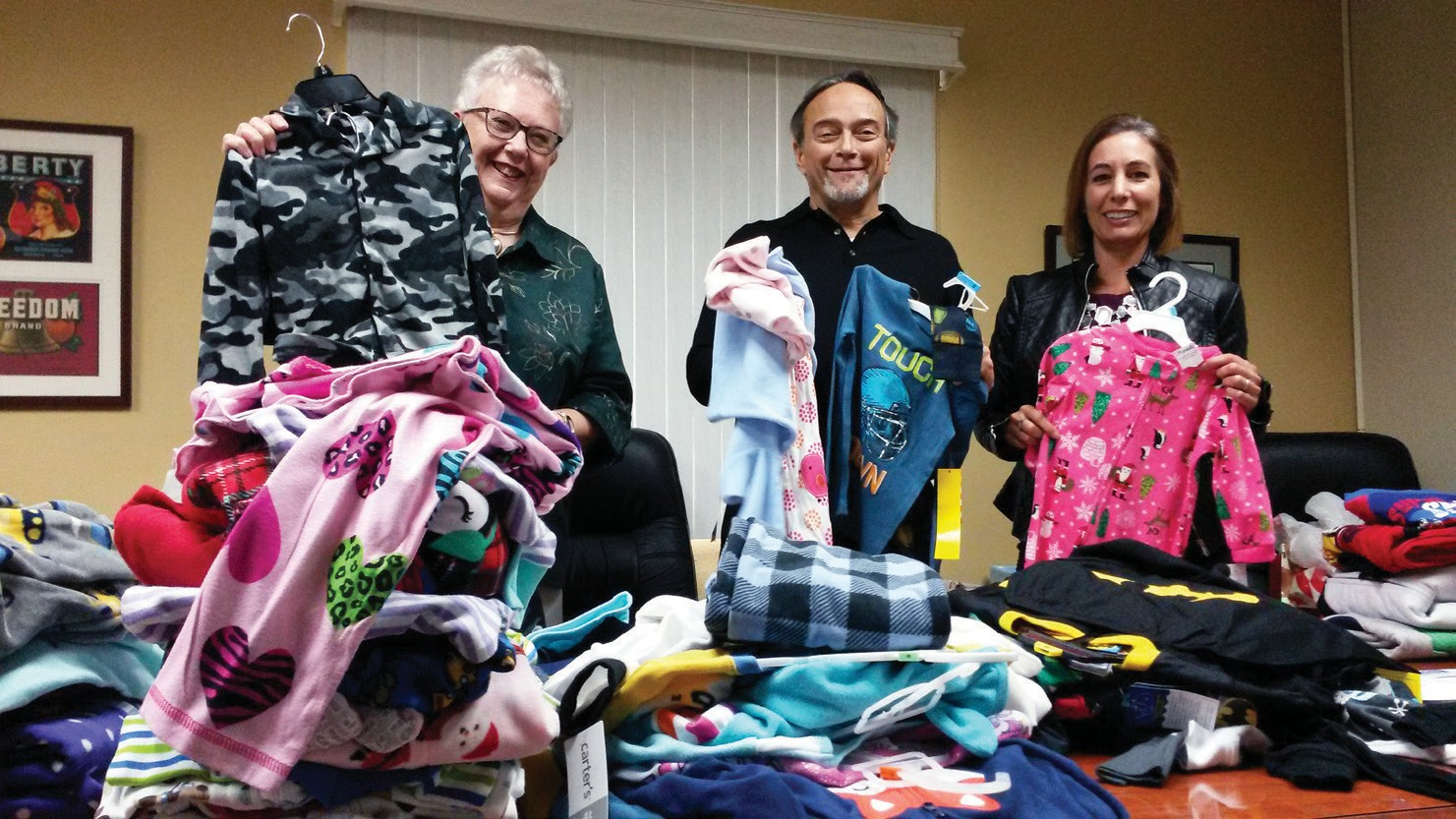 Kitty Aeling, Kevin Svetich and Rorie Johnston of the Escondido Chamber of Commerce are shown sorting through the PJ's.