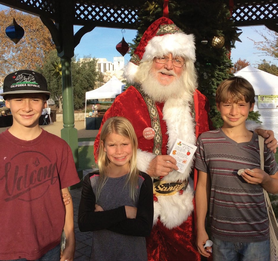 Santa with three health conscious youngsters he met at the Escondido Farmers Market.