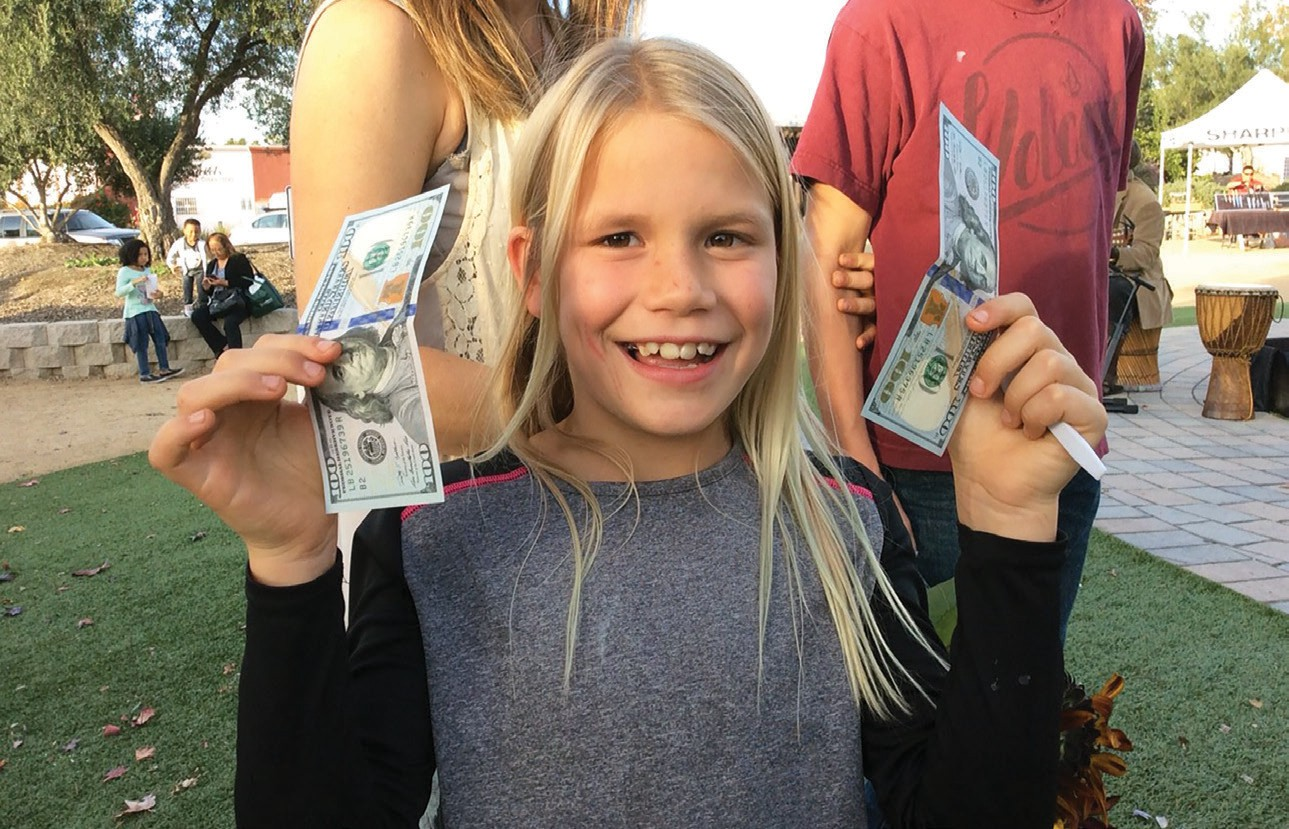 One of the children shows off the $100 bills that were presented to her and her two brothers by members of the Escondido Police Department, upon recommendation by Santa.