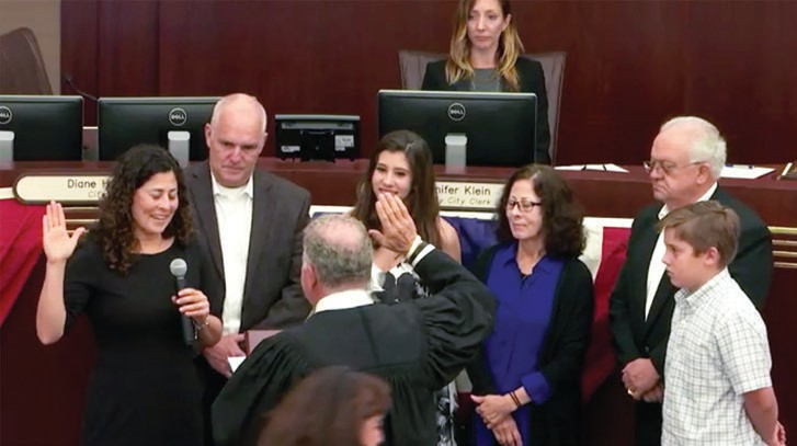 Olga Diaz, left, joined by her family is sworn in for a third term on the city council.