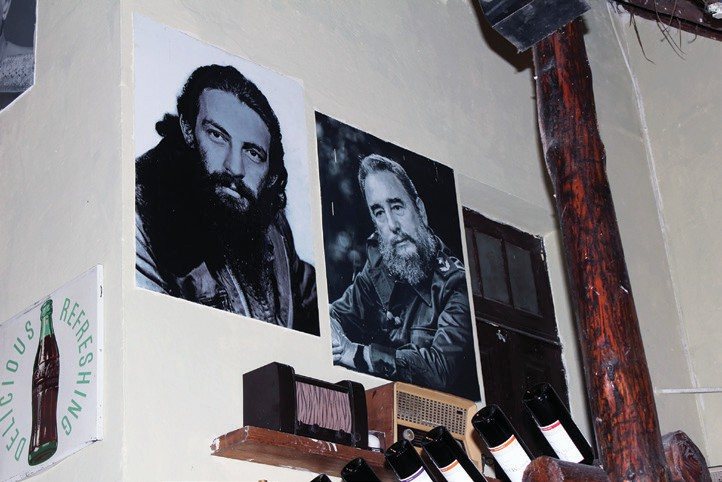 Posters of Cuban revolutionaries, including Che Guevara and Fidel Castro, displayed in a tourist oriented restaurant.