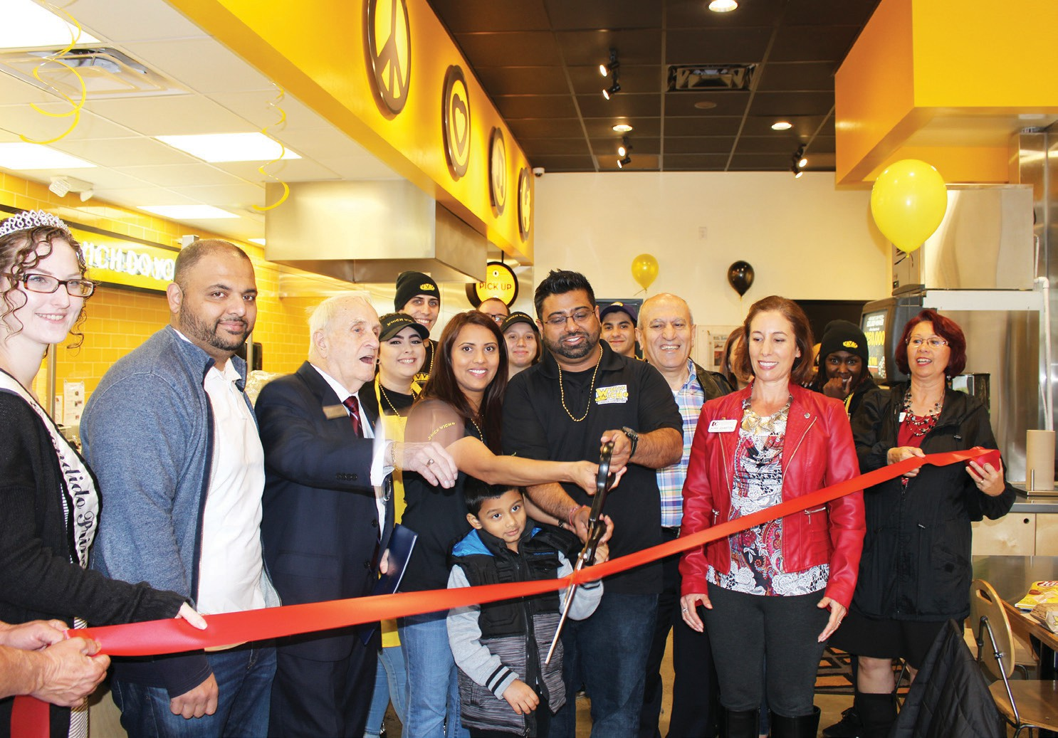 Despite the heavy rain, the Chamber of Commerce and local dignitaries showed up in force Friday to celebrate the ribbon cutting for the Escondido Which Wich. Gen. Mgr. Vimal Patel, his family, Mayor Sam Abed, Princess Amanda Cowie, and Chamber CEO Rorie Johnston were among those taking part.