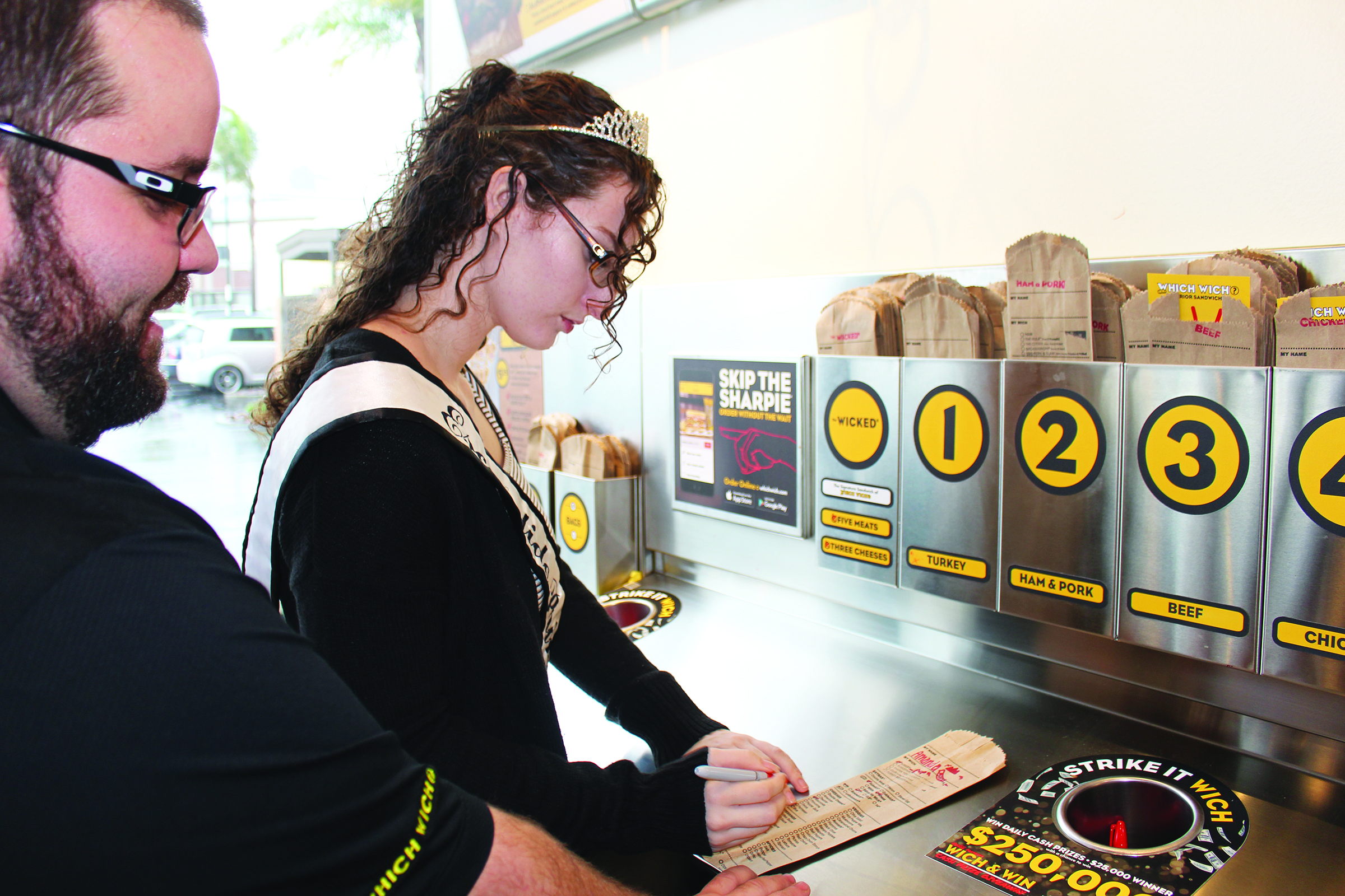 Douglas Jones, head of operations for the Escondido Which Wich, helps Escondido Princess Amanda Cowie fill out her order bag.